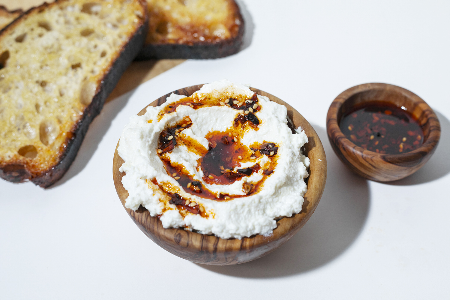 whipped ricotta with momofuku chili crunch in a bowl
