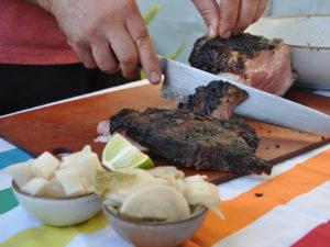 slicing through grilled pork collar
